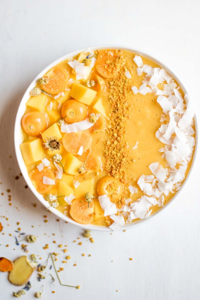 Fresh turmeric smoothie bowl, the perfect morning treat! Banana free! The creamy base is cauliflower, mango, lemon, orange, and a few other superfood ingredients to help you beat those seasonal allergies. So yummy!