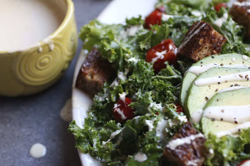 This vegan Kale Caesar Salad with roasted tomatoes and creamy avocado is easy to make super healthy and nourishing. |abraskitchen.com