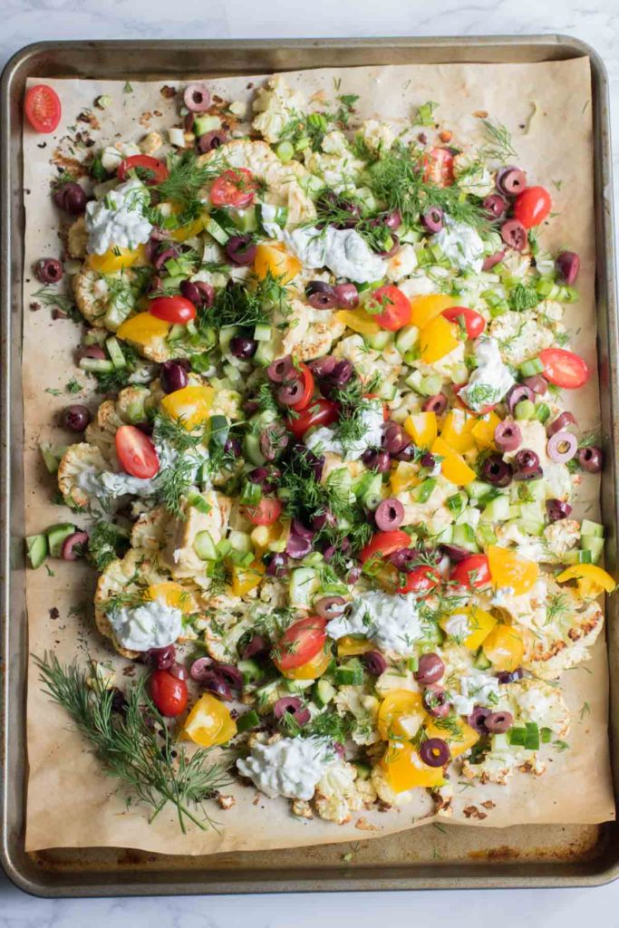 Loaded Mediterranean Cauliflower Nachos are piled high with creamy feta cheese, crunchy cucumbers, hummus, olives, tzatziki sauce and more! So delicious you won't want to share. | abraskitchen.com