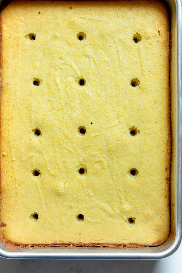 holes in a poke cake ready for strawberry sauce