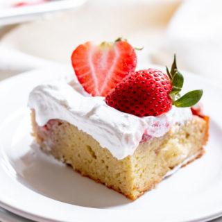 slice of Paleo Strawberry Poke Cake on white background