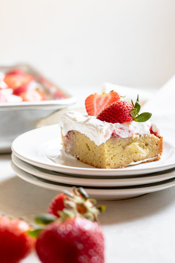 3 small stacked plates with Paleo Strawberry Poke Cake