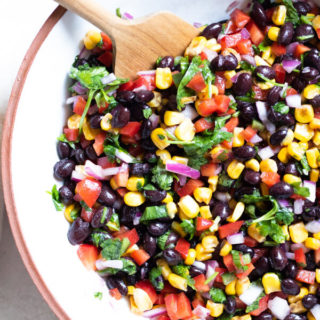 Healthy Corn and Black Bean Salad in a white bowl with a wooden spoon on a white background