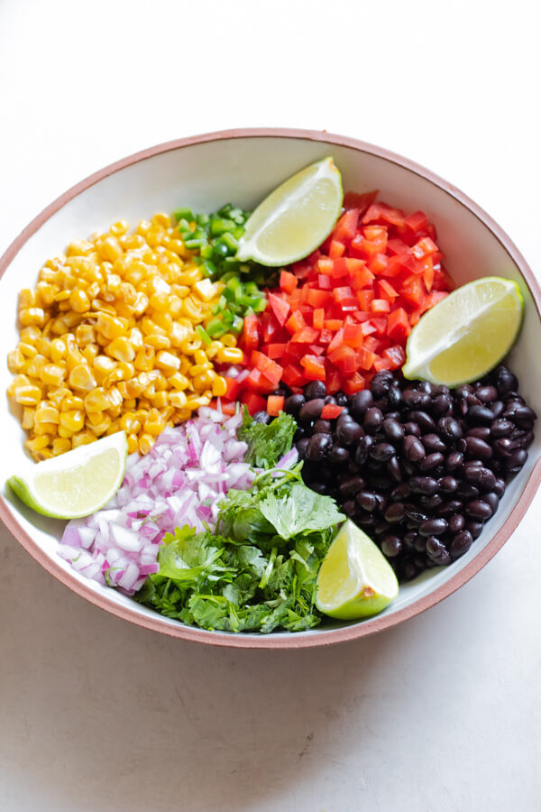 Ingredients needed for Healthy Corn and Black Bean Salad in a white bowl on white background
