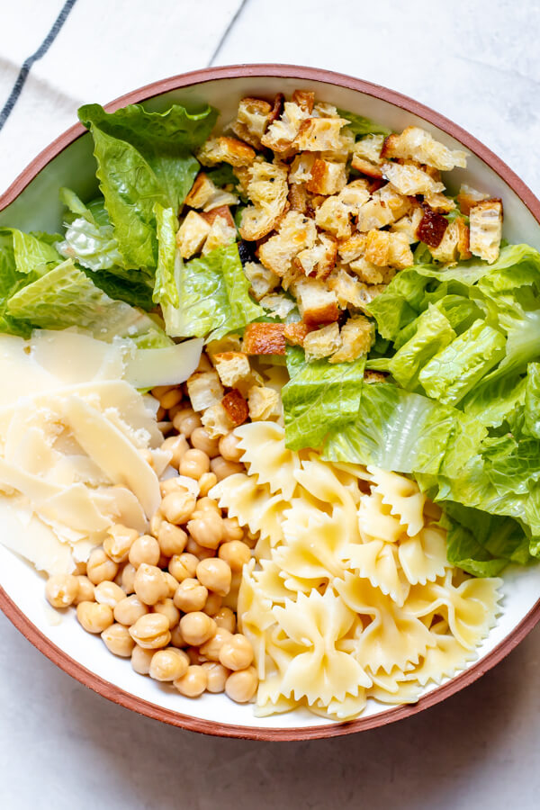 ingredients in a bowl for Chickpea Caesar Pasta Salad
