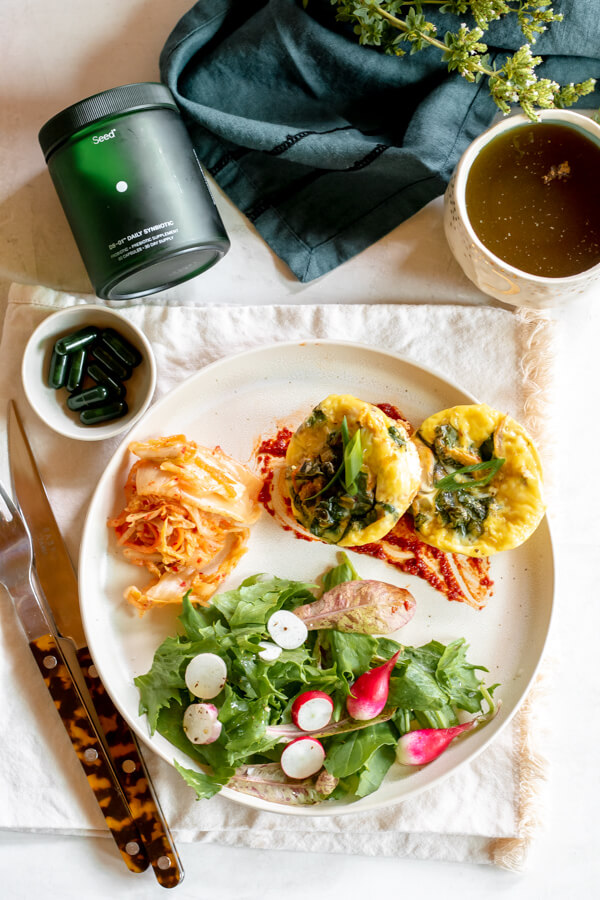 white plate of egg muffins, salad and kimchi with probiotics