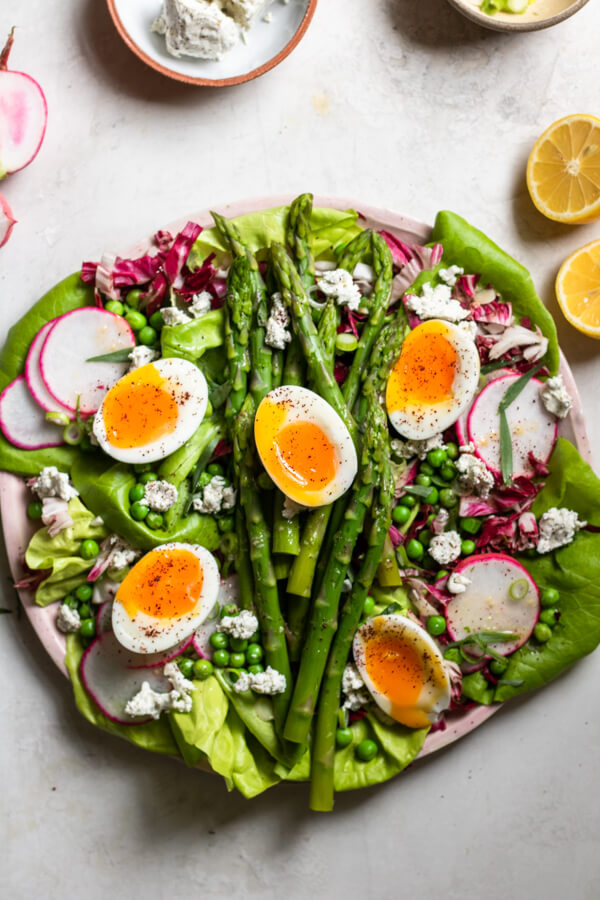 Insanely Delicious Asparagus Salad on a pink plate on a white background