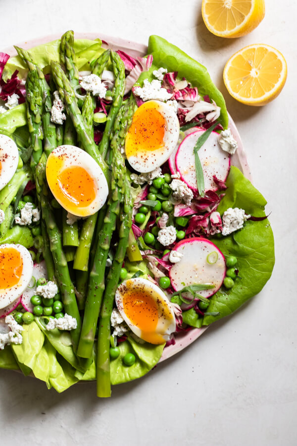 Insanely Delicious Asparagus Salad on a pink plate on a white background close up of lemons and eggs