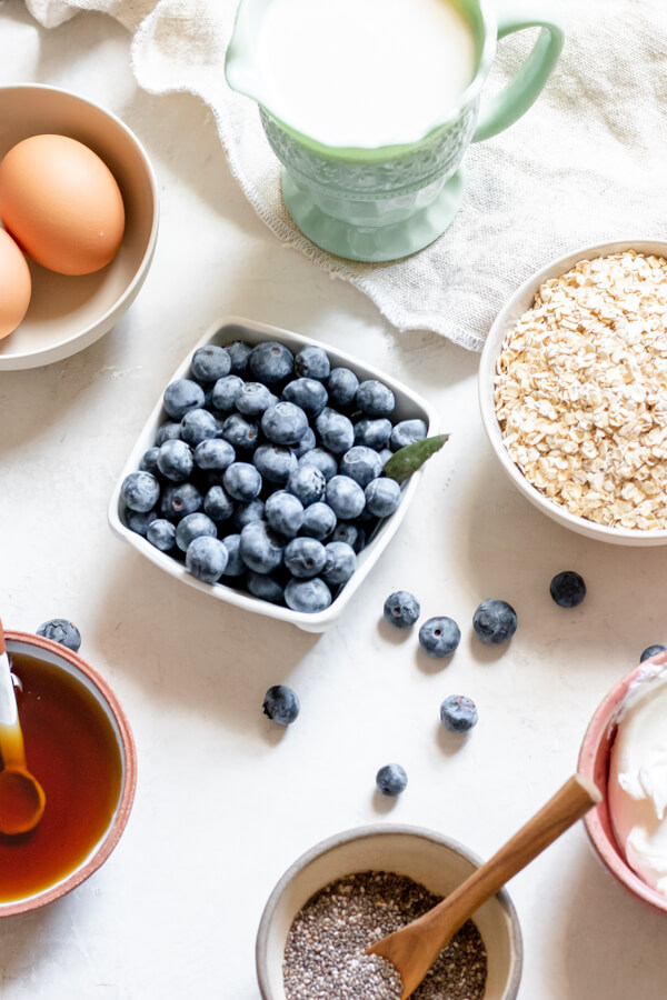Ingredients for baked blueberries and cream oatmeal, blueberries, oats, eggs, yogurt, maple syrup, almond milk, chia seeds