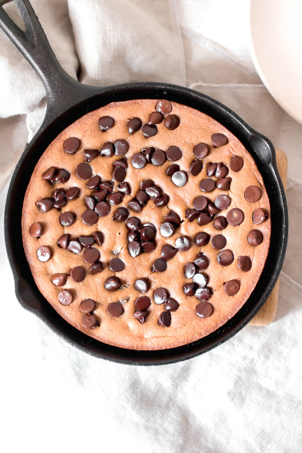 Gooey rich and decadenttahini chocolate chip cookie made in a skillet. A giant cookie that is sure to bring a smile to your face! Real food, gluten-free, no flour, or refined sugar.