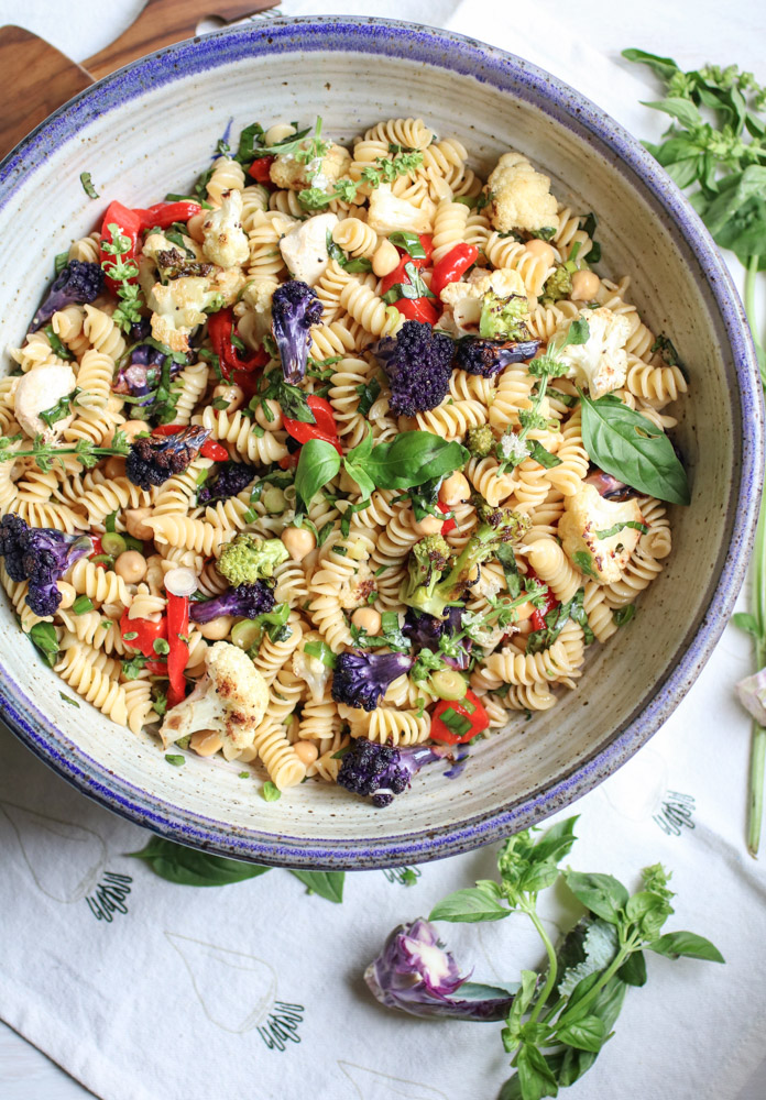 Fresh Basil and Roasted Cauliflower pasta salad - roasted cauliflower, fresh mozzarella, chickpeas, roasted bell peppers, and tons of fresh basil. This is the easiest and healthiest vegetarian pasta salad. | abraskitchen.com