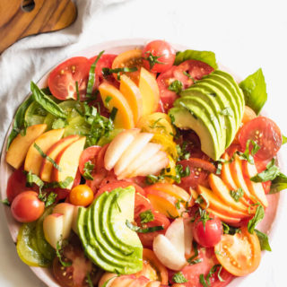 A fresh heirloom tomato salad with juicy sweet peaches, creamy avocado, and fresh herbs. This healthy, simple salad is the very representation of savoring the final weeks of summer using only seasonal local produce.