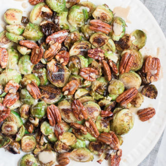 Gorgeous roasted Brussels sprouts tossed with crunchy pecans in a brown butter sauce and drizzled with a spiced maple tahini glaze.