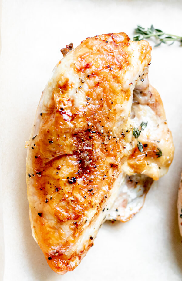 roasted split chicken breast on a white background
