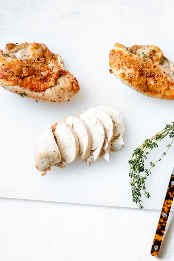 roasted split chicken breast on a cutting board with fresh thyme