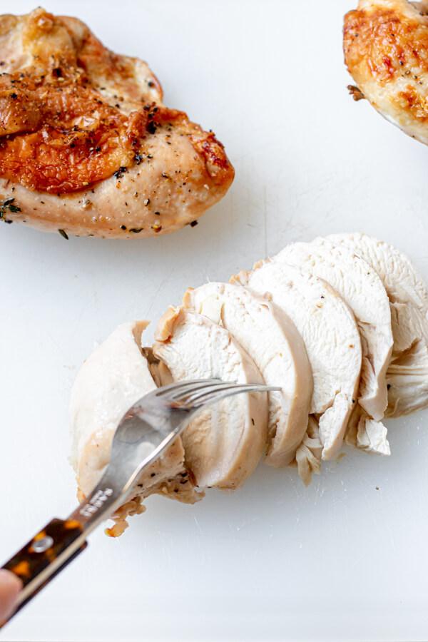 Juicy roasted split chicken breast on a cutting board