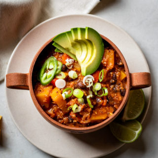 Quinoa Butternut Squash Chili in terracotta bowl on pink plate