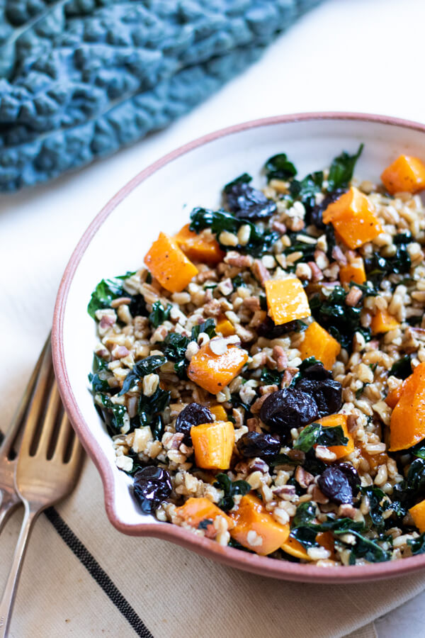 Butternut Squash and Kale Farro Salad with Dried Cherries and Pecans in white bowl on white background