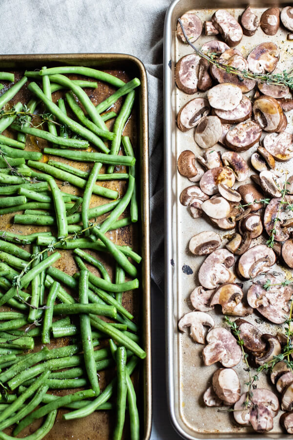 Roasted green beans on a sheet pan and roasted mushrooms on a sheet pan