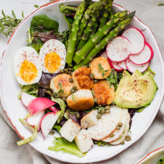 scallop nicoise salad on white bowl with asparagus and radishes and veggies