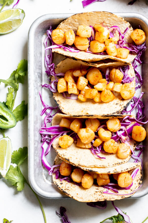 seared scallops in tortilla shells on a sheet tray with purple cabbage