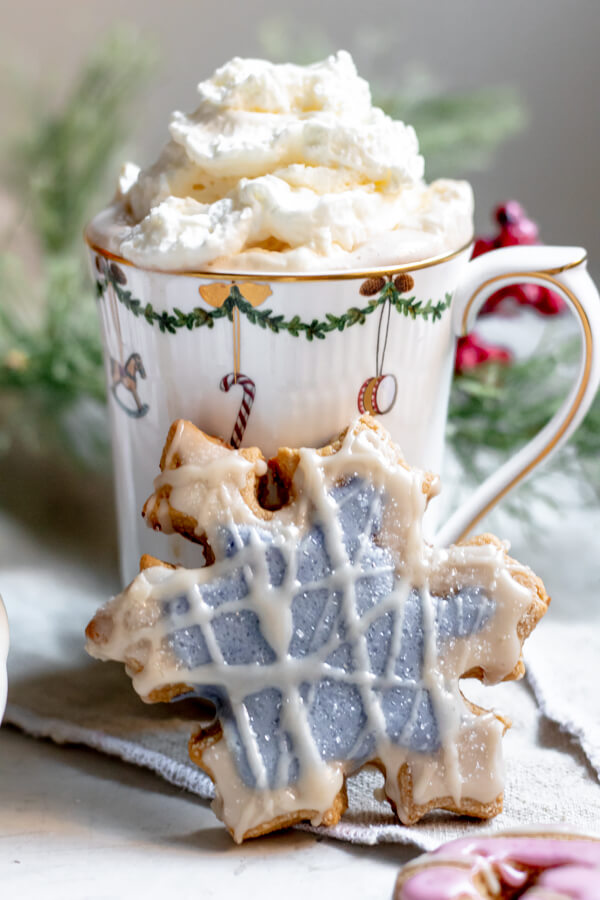 almond flour cut out cookie leaning against a holiday mug of hot chocolate
