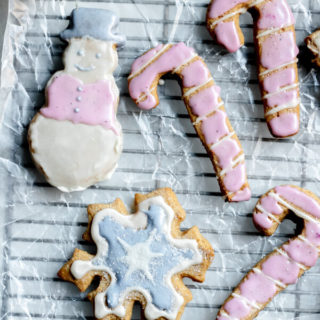 holiday sugar cookies made with almond flour on a cooling rack, iced with natural frosting