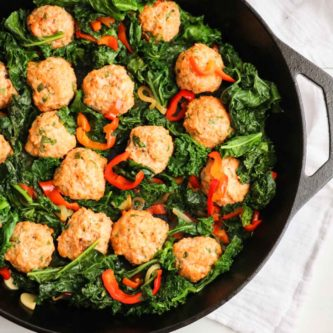 The BEST chicken meatballs in a creamy roasted red pepper feta cheese sauce with sauteed kale. One skillet and OMG, so good! |Abraskitchen.com